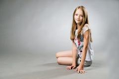 Retrato de una muchacha hermosa en un fondo gris Fotos de archivo libres de regalías