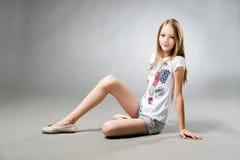 Retrato de una muchacha hermosa en un fondo gris Imagen de archivo libre de regalías