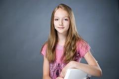 Retrato de una muchacha hermosa en un fondo gris Imágenes de archivo libres de regalías