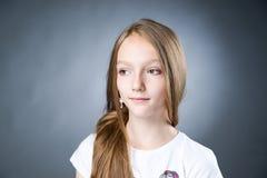 Retrato de una muchacha hermosa en un fondo gris Foto de archivo
