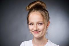 Retrato de una muchacha hermosa en un fondo gris Fotografía de archivo