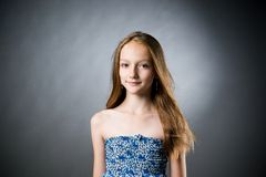 Retrato de una muchacha hermosa en un fondo gris Foto de archivo libre de regalías