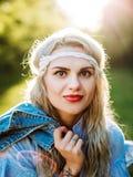Retrato de una muchacha hermosa en un vestido azul con un dolor de cabeza en un campo en la puesta del sol en verano Ropa casual  foto de archivo libre de regalías