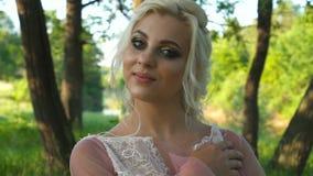Retrato de una muchacha hermosa en un vestido blanco en un campo con los oídos en la puesta del sol en verano almacen de video