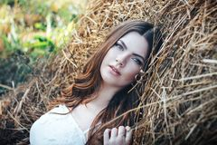 Retrato de una muchacha hermosa en un vestido blanco en el campo en la puesta del sol en verano Foto de archivo libre de regalías