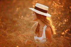 Retrato de una muchacha hermosa en un vestido y un sombrero blancos en el fie foto de archivo