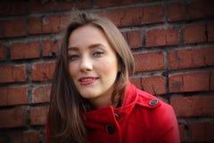 Retrato de una muchacha hermosa en una capa roja en un backg de la pared de ladrillo fotos de archivo