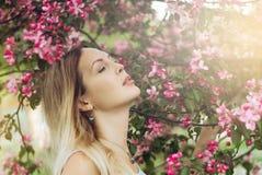Retrato de una muchacha hermosa entre follaje y flores de la primavera foto de archivo libre de regalías