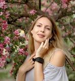 Retrato de una muchacha hermosa entre follaje y flores de la primavera fotografía de archivo