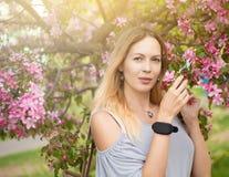 Retrato de una muchacha hermosa entre follaje y flores de la primavera imágenes de archivo libres de regalías