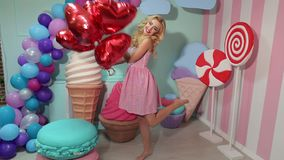 Retrato de una muchacha hermosa joven con los globos rojos en un fondo brillante almacen de video