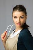 Retrato de una muchacha hermosa joven con ropa y vidrios largos de trabajo del pelo que llevan oscuro Foto de archivo libre de regalías