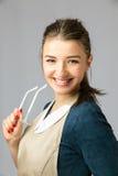 Retrato de una muchacha hermosa joven con ropa y vidrios largos de trabajo del pelo que llevan oscuro Fotografía de archivo