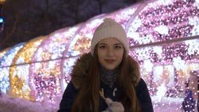 Retrato de una muchacha hermosa joven En el invierno por la tarde Ella se calienta las manos en manoplas metrajes