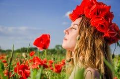 Retrato de una muchacha hermosa joven en un campo de la amapola con una guirnalda de amapolas en su cabeza en un día soleado cali Fotos de archivo libres de regalías