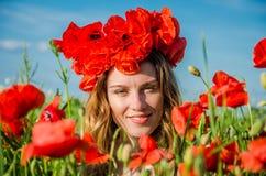 Retrato de una muchacha hermosa joven en un campo de la amapola con una guirnalda de amapolas en su cabeza en un día soleado cali Imagenes de archivo