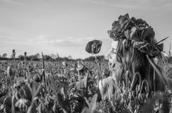 Retrato de una muchacha hermosa joven en un campo de la amapola con una guirnalda de amapolas en su cabeza en un día soleado cali Foto de archivo