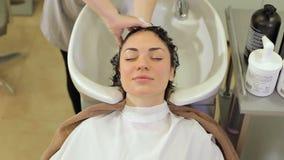 Retrato de una muchacha hermosa joven en un sal?n de belleza mientras que lava su cabeza metrajes