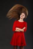 Retrato de una muchacha hermosa joven sonriente en un vestido rojo con a Imagenes de archivo