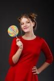 Retrato de una muchacha hermosa joven sonriente en un vestido rojo con a Imágenes de archivo libres de regalías