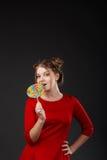 Retrato de una muchacha hermosa joven sonriente en un vestido rojo con a Imagen de archivo