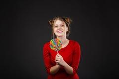 Retrato de una muchacha hermosa joven sonriente en un vestido rojo con a Imagen de archivo libre de regalías