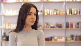 Retrato de una muchacha hermosa, que mira la cámara y la sonrisa en el salón de belleza almacen de video