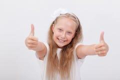 Retrato de una muchacha hermosa que muestra los pulgares para arriba encendido Fotos de archivo libres de regalías