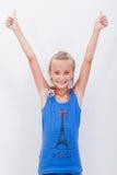 Retrato de una muchacha hermosa que muestra los pulgares para arriba encendido Foto de archivo libre de regalías