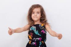Retrato de una muchacha hermosa que muestra los pulgares para arriba encendido Imágenes de archivo libres de regalías