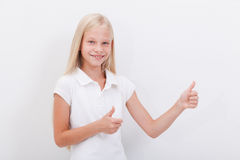 Retrato de una muchacha hermosa que muestra los pulgares para arriba encendido Foto de archivo