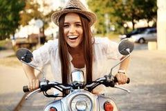 Retrato de una muchacha hermosa que se sienta en la vespa retra de plata, sonriendo y mirando la cámara Foto de archivo libre de regalías