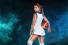 Retrato de una muchacha hermosa y atractiva con un baloncesto en estudio Concepto del deporte imágenes de archivo libres de regalías