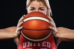 Retrato de una muchacha hermosa y atractiva con un baloncesto en estudio Concepto del deporte aislado en fondo negro imagenes de archivo