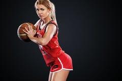 Retrato de una muchacha hermosa y atractiva con un baloncesto en estudio Concepto del deporte aislado en fondo negro fotografía de archivo