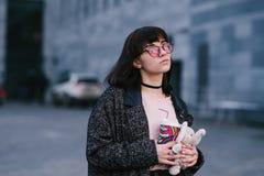 Retrato de una muchacha hermosa y elegante en los vidrios que sostienen un café y un juguete suave en el fondo de la ciudad Imagenes de archivo