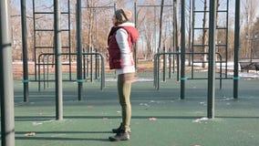 Retrato de una muchacha juguetona en el sombrero del invierno y el amarillo caliente que hacen los ejercicios en el cojín del ent almacen de video
