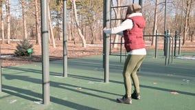 Retrato de una muchacha juguetona en el sombrero del invierno y el amarillo caliente que hacen los ejercicios en el cojín del ent almacen de metraje de vídeo