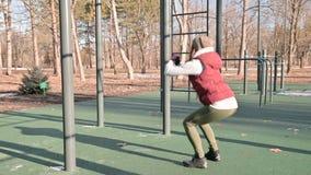 Retrato de una muchacha juguetona en el sombrero del invierno y el amarillo caliente que hacen los ejercicios en el cojín del ent metrajes