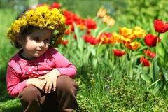 Retrato de una muchacha linda de dos años que lleva una guirnalda del diente de león, sentándose cerca de los tulipanes foto de archivo libre de regalías
