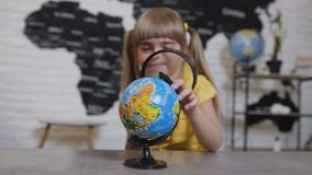 Retrato de una muchacha linda que juega la mirada en lupa Muchacha que mira con una lupa y los estudios almacen de metraje de vídeo