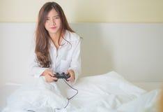 Retrato de una muchacha linda que juega a los videojuegos mientras que ella es o de mentira Foto de archivo