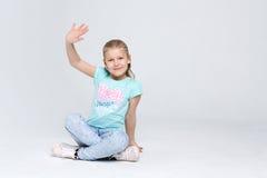 Retrato de una muchacha linda que se sienta en el piso en el fondo blanco Imagen de archivo libre de regalías