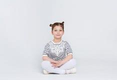 Retrato de una muchacha linda que se sienta en el piso en el fondo blanco Foto de archivo libre de regalías