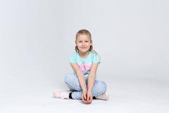 Retrato de una muchacha linda que se sienta en el piso en el fondo blanco Fotografía de archivo libre de regalías