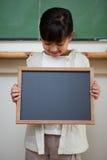 Retrato de una muchacha linda que sostiene una pizarra de la escuela Imagen de archivo libre de regalías