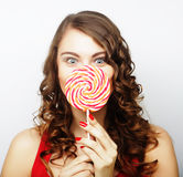 Retrato de una muchacha linda sonriente que cubre sus labios con la piruleta Fotografía de archivo