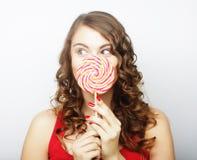 Retrato de una muchacha linda sonriente que cubre sus labios con la piruleta Fotos de archivo