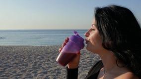 Retrato de una muchacha morena atractiva que bebe una sacudida de la proteína de una botella de los deportes en el fondo del mar
