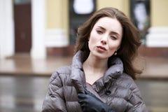 Retrato de una muchacha morena elegante joven en del gris una chaqueta abajo Imagenes de archivo